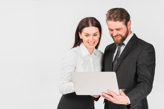 Colleagues male and female smiling and looking at laptop
