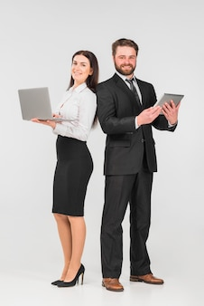 Colleagues male and female standing with gadgets and smiling