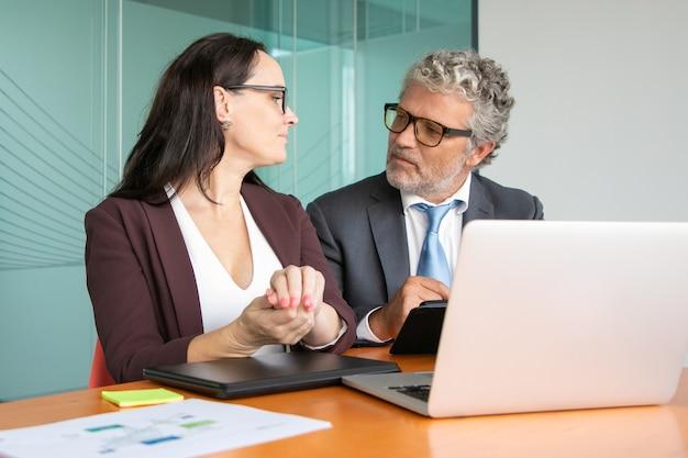 同僚のプロジェクトの会議と議論、開いているラップトップでテーブルに座っている、タブレットを使用して話している。