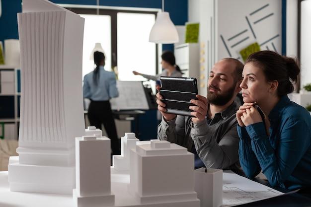 建築専門家の同僚は、デジタル技術のためにオフィスで働いています