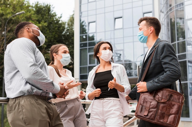 Colleagues outdoors during pandemic chatting with masks
