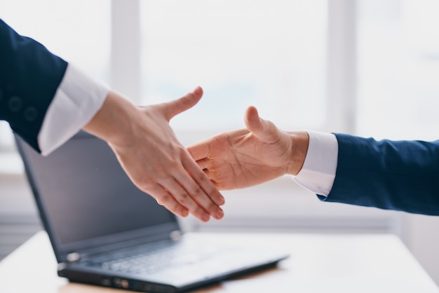 Colleagues shaking hands successful deal office laptop professionals. high quality photo
