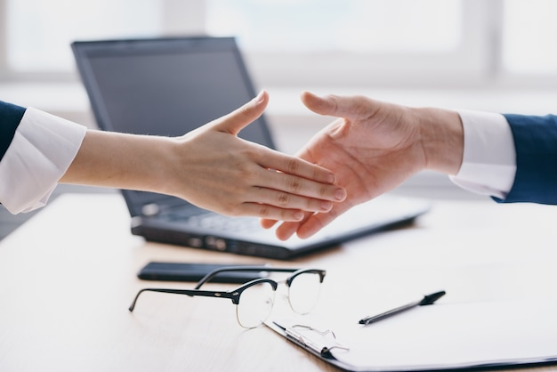 Colleagues shaking hands successful deal office laptop professionals
