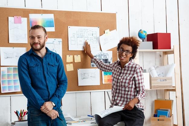 同僚が笑顔で話し、図面や新しいアイデアについて話し合う