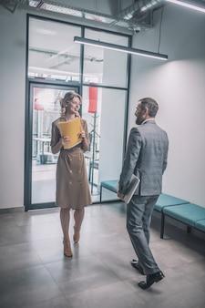 同僚。オフィスの廊下でドキュメントを持つ同僚の男性に向かって歩いているフォルダを持つ若い女性の笑顔