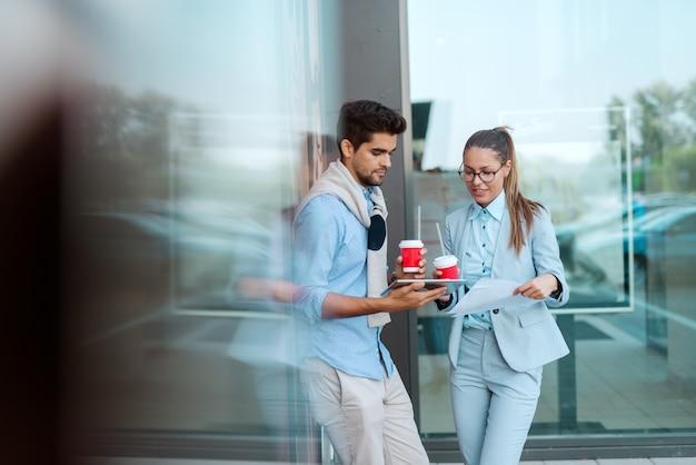 屋外で立って、タブレットを見ながらコーヒーを飲む同僚。