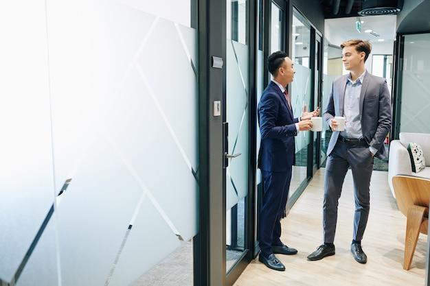 Colleagues talking in office corridor