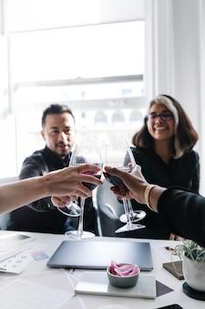 職場でワイングラスを乾杯する同僚