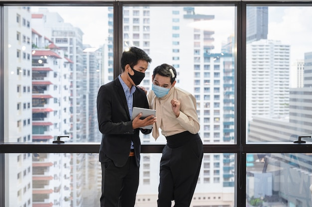 Colleagues wearing face mask consulting the business plan on tablet, asian businessman discussing with gay manager in modern office