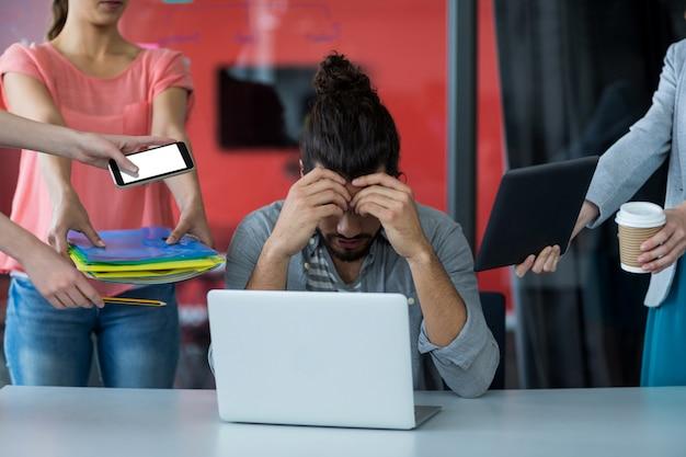 Коллеги с цифровым планшетом и мобильным телефоном разговаривают с расстроенным человеком