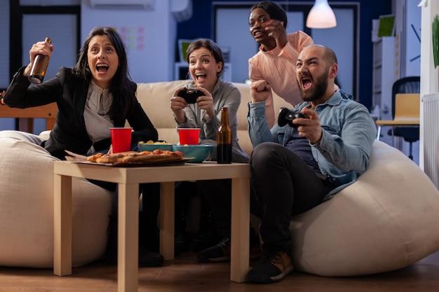 テレビでコンソールゲームをプレイした後、多様な民族の同僚がオフィスで一体感を楽しんでいます。屋内のお祝いパーティーで楽しい娯楽を持っている多民族の労働者
