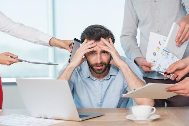 Коллеги с документом, цифровым планшетом и мобильным телефоном разговаривают с разочарованным человеком