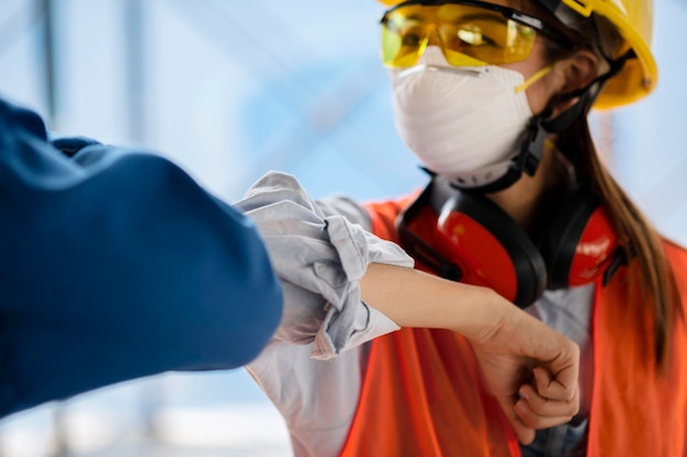 Colleagues with safety equipment touching elbow
