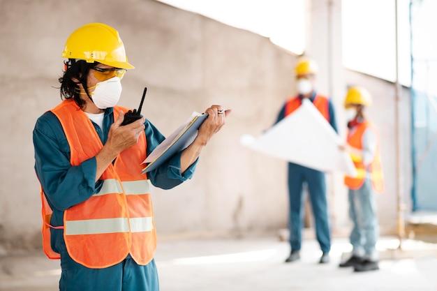 Коллеги с защитным оборудованием, работающим с чертежами