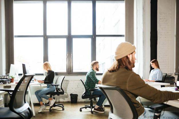 동료들은 사무실에서 컴퓨터를 사용하여 일합니다. 옆으로 찾고 있습니다.