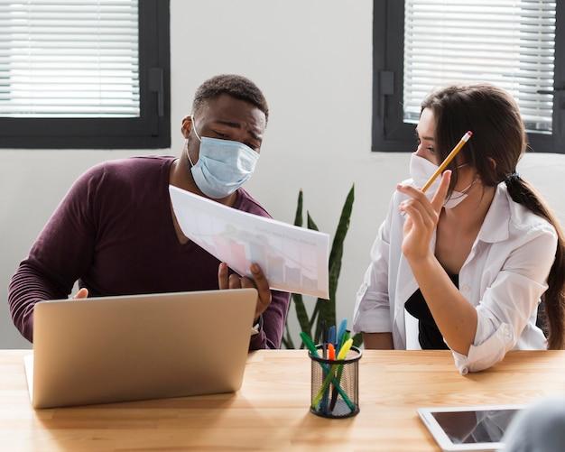 Colleghi al lavoro in ufficio durante la pandemia indossando maschere mediche