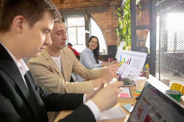 Коллеги работают вместе в офисе с помощью современных устройств во время творческой встречи. канцелярские товары, ноутбук, документы. концепция бизнеса, офиса, финансов, открытого пространства.
