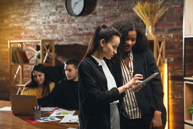 Коллеги работают вместе в современном офисе с помощью устройств и гаджетов во время творческой встречи