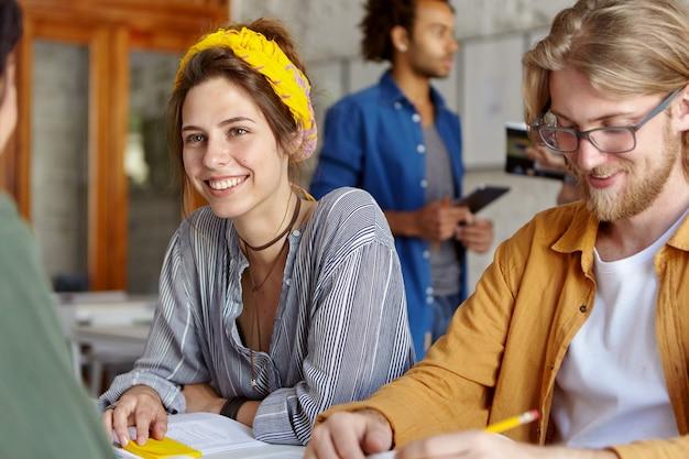 Colleghi che lavorano insieme seduti nella caffetteria