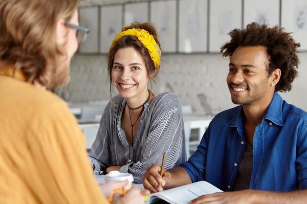 Коллеги работают вместе, сидя в кафе