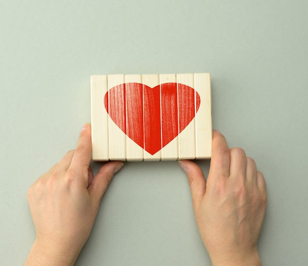 Collected red heart on wooden bars held by two hands