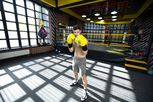 Собранный спортсмен в боксерском зале отрабатывает боксерские удары во время тренировки
