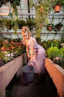꽃 수집. 온실에서 꽃을 수집하려는 동안 양동이를 들고 좋은 매력적인 여자