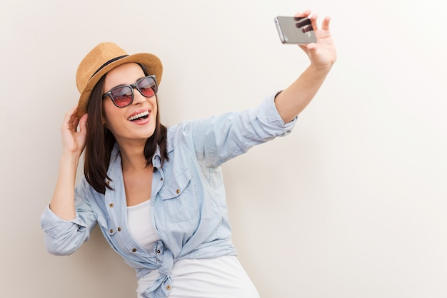 Collecting memories. portrait of beautiful young woman in glasses adjusting her hat while making selfie and standing against brown background