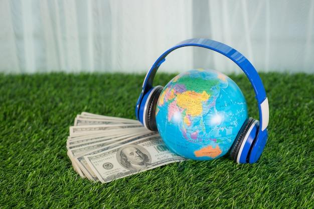 잔디 배경에 세계지도와 이어폰으로 여행을 위해 돈을 모으기