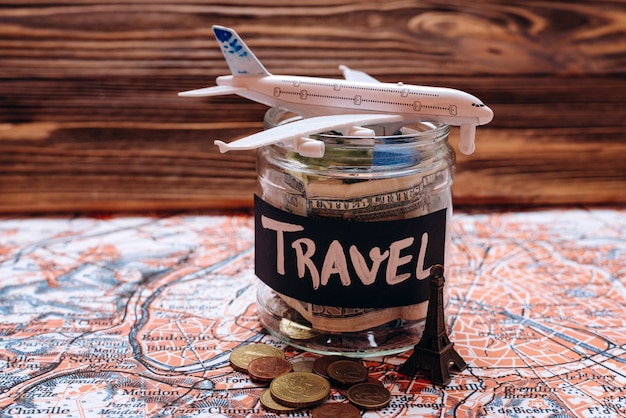 Collecting money for travel, money savings in a glass jar with world map