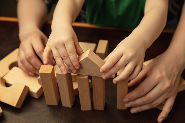 Collecting wooden constructor like house. close up shot of female and kid's hands doing different things together. family, home, education, childhood, charity concept. mother and son or daughter.