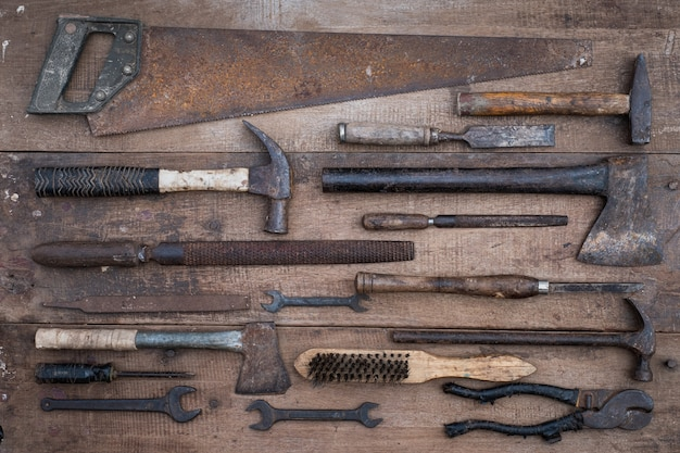 Collection of antique woodworking handtools on a rough workbench old wooden