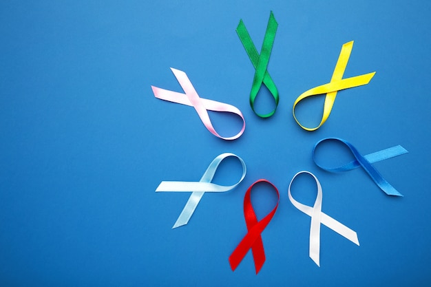 Collection of awareness ribbons on blue surface