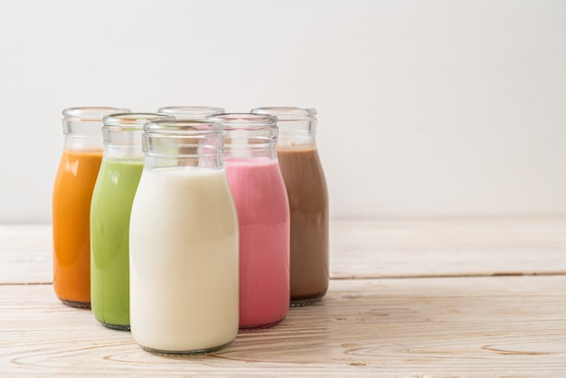 Collection of beverage thai milk tea, matcha green tea latte, coffee, chocolate milk, pink milk and fresh milk in bottle on wood table