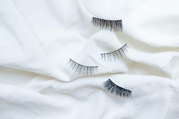 Collection of black false eyelashes on cotton white background