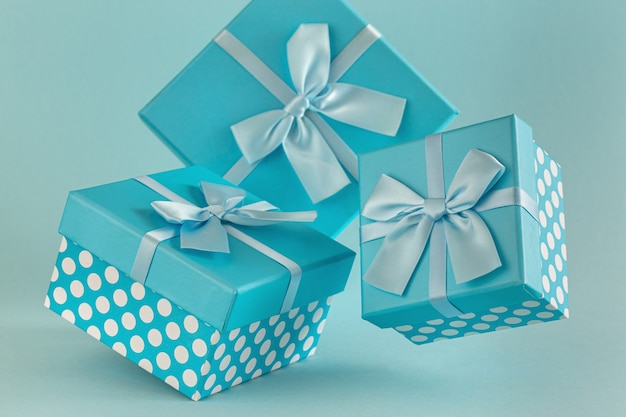 Collection of blue gift boxes with ribbons on blue background copy space