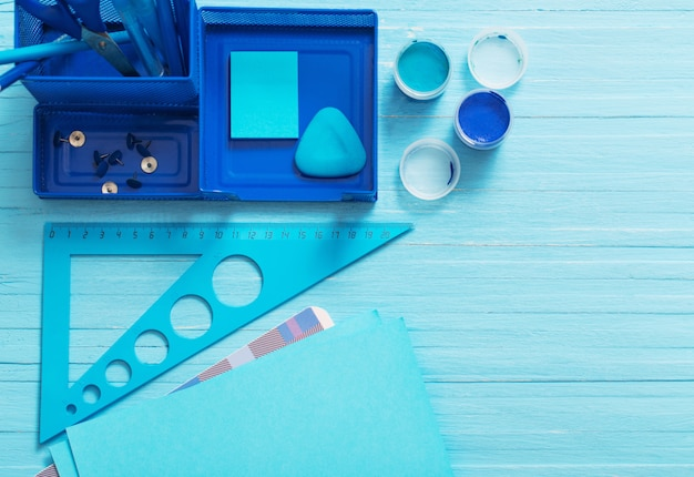 Collection of blue school supplies on blue wooden table