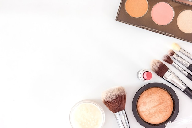 A collection of brush, make up and cosmetic beauty products arranged on a white background
