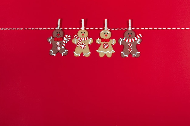 Collection of christmas decorations on the christmas tree gingerbread man hanging on a rope in the form of a handmade garland. new year and gift concept