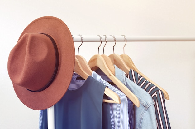 Collection of clothes with brown hat hanging on rack near white wall. clothes for women in blue colors. office style.