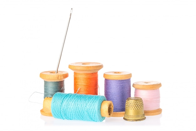 Collection of color thread spools with needle and thimble isolated on white background
