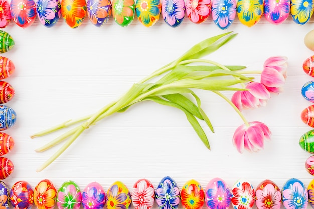 Collection of colored eggs on edges and flowers