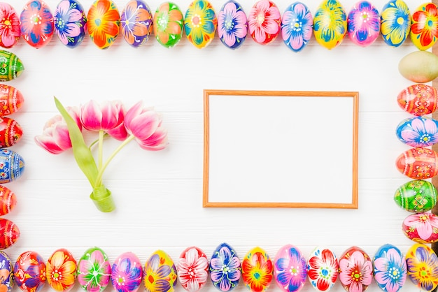 Collection of colored eggs on edges, frame and flowers