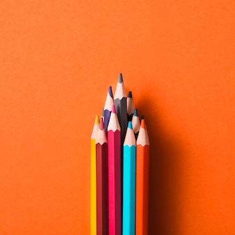 Collection of colored pencils on an orange background
