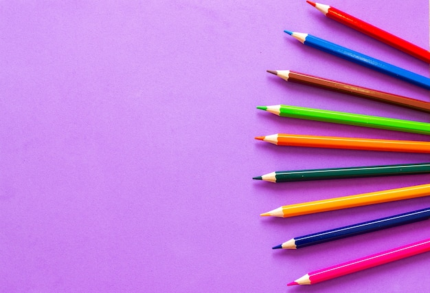 Collection of colored pencils on a purple background top view and copy space.