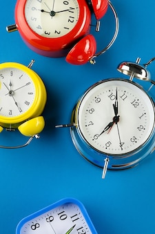 Collection of colorful alarm clocks in retro vintage style on a bright blue surface. banner.