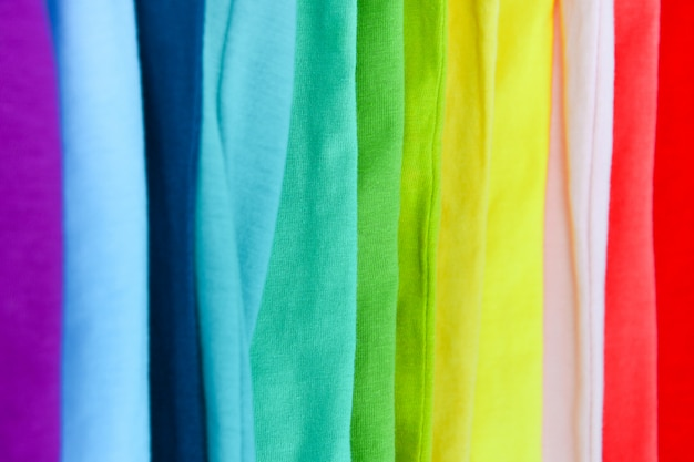 Collection of colorful rainbow t-shirts hanging on clothes hanger in closet