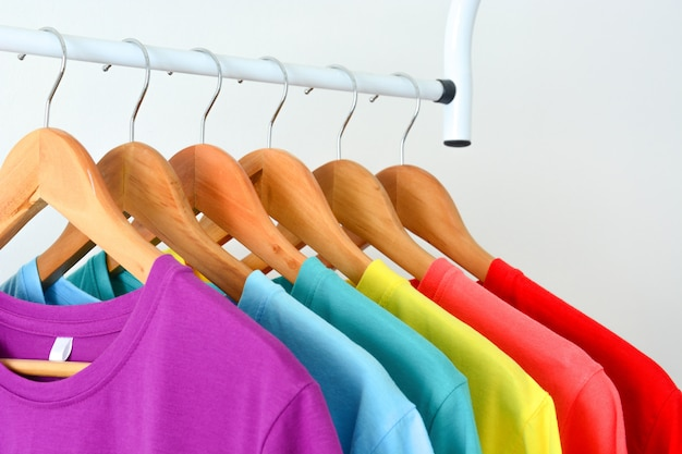 Collection of colorful rainbow t-shirts hanging on wooden clothes hanger on clothing rack