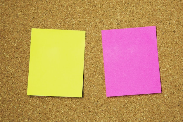 Collection of colorful variety post it. paper note reminder sticky notes pin on cork bulletin board.