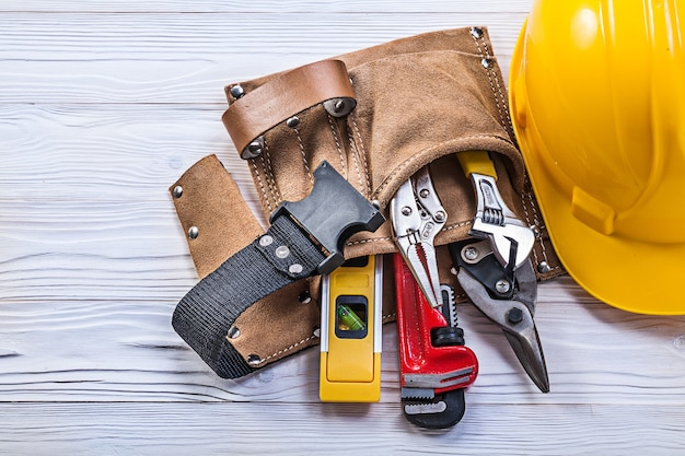Collection of construction tooling in leather tool belt safety building helmet on wooden board